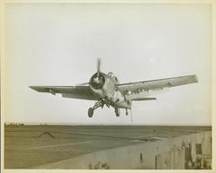 Photograph, Grumman FM1 Wildcat over flight deck of U. S. S. Casablanca, Robert K. Lohman, Ens. Pilot